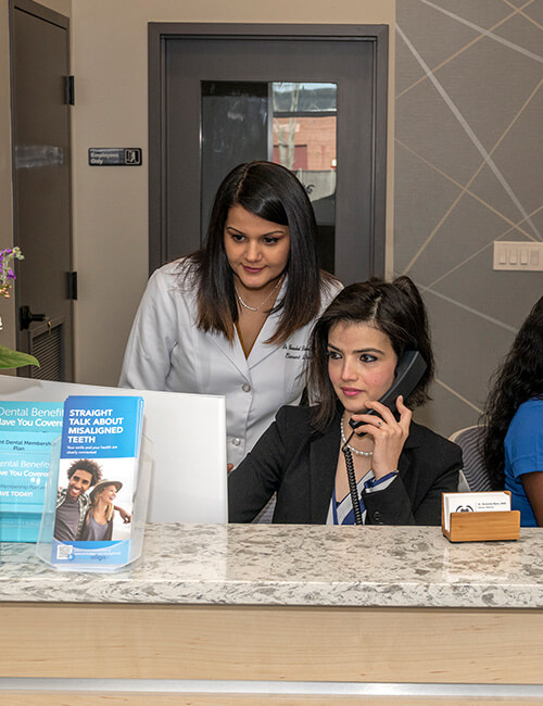 Dr. Bains on front desk with administrative staff
